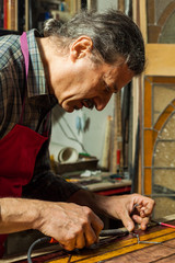Artisan making Stained Glass panels in his Workshop