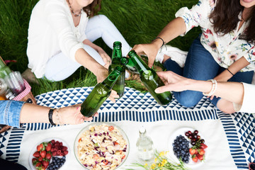 Unrecognizable women toasting with beer in park