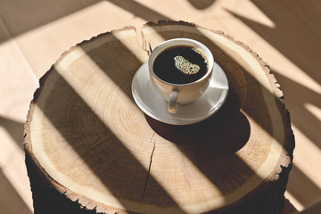 Cup of coffee on a wood log