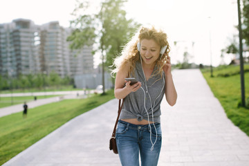 Young blond woman listening to music outdoors