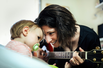 Mother Playing Guitar at Home with Her Adorable Little Girl
