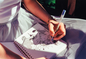 Closeup of a woman drawing doodles in her sketch book