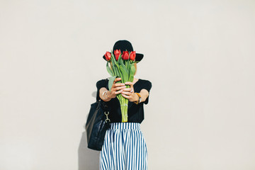 Portrait of a stylish senior woman hiding her face with a bouquet of red tulips.