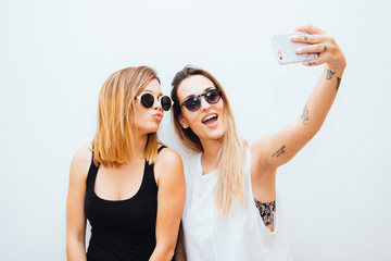 Two women taking a selfie with your mobile phone