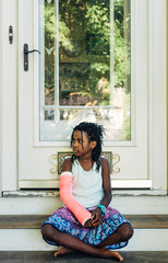 Black girl with pink cast sitting on steps
