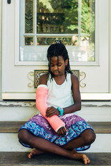 Black girl looking at her pink cast