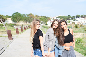 Three friends on pier smiling at camera