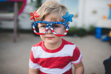 Young boy wearing patriotic glasses for fourth of july
