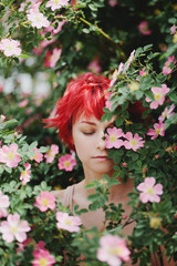Portrait of red-haired girl hid behind a flowering wild rose