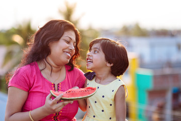 Mother and daughter sharing a cheerful moment while eating watermelon