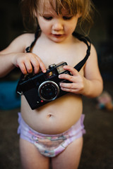 Toddler girl playing with an old camera.