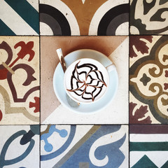 A mocha cappuccino laying on a colorful set of ornamental tiless
