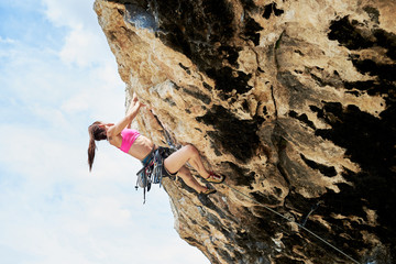Female climber climbing the extreme cliff