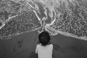 Black and white portrait of a young kid observing the waves on the shore
