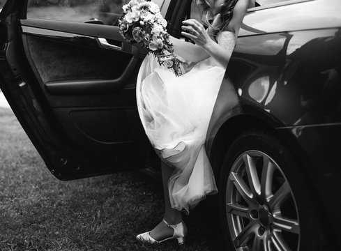 bride in white wedding dress getting out of a car in black and white