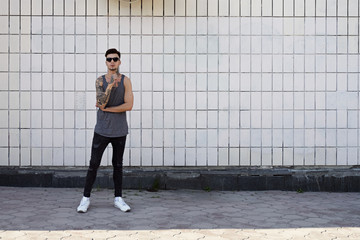 Young man with tattoos in sunglasses against of white ceramic wall