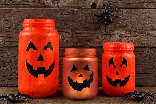 Mason jar Halloween Jack o Lanterns against an old wood background
