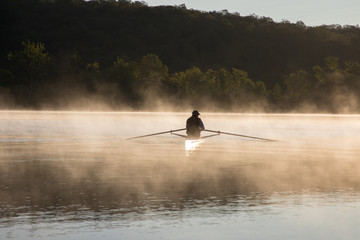 Silhouetted Man Sculling at Sunrise on Water with Fog