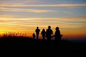 in sunrise, silhouette of a people walking on mountains