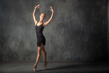 Young beautiful woman prima theater in a black pack, white pantyhose, white pointe shoes beautifully dances Russian ballet in a black dance studio
