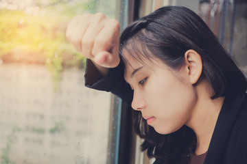woman feeling sad at window . lonely