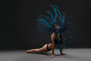 Girl with blue dreadlocks photo against black wall