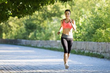 Young smiling sporty woman running in park in the morning. Fitness girl jogging in park