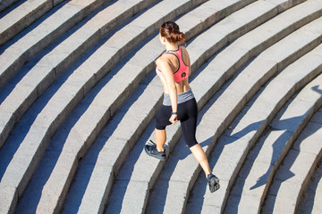 Young slim woman in pink top running on stairs in the morning city. Healthy lifestyle background with copyspace