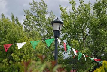 Wimpelkette in rot-grün-weiß an einer Straßenlaterne anlässlich des mexikanischen Nationalfeiertags