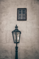 An ancient lamp and a window on the dirty facade of an old house.