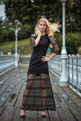 Outdoor lifestyle portrait of blonde young woman in stylish black dress staying on bridge on the street. Autumn, rainy day