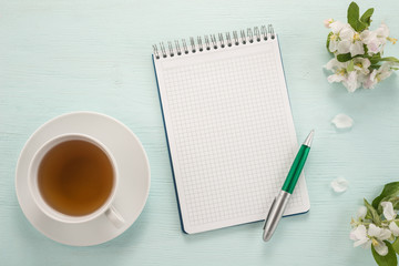 Notepad, pen, flowers and cup of tea