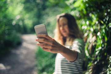 Young woman taking selfie in the forest