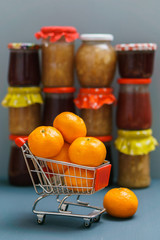 Mandarines in the shopping cart on the background with jam pots