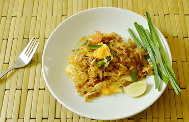 Pad Thai stir fried rice noodles with dry shrimp and yellow tofu on plate