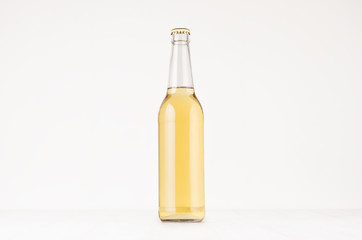 Transparent longneck beer bottle 500ml with lager, mock up. Template for advertising, design, branding identity on white wood table.