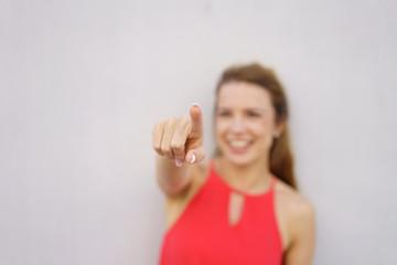 lachende frau zeigt mit dem finger nach vorne