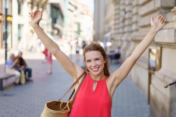 frau geht einkaufen und streckt lachend die arme nach oben