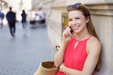 lächelnde frau steht in der stadt und telefoniert