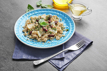 Salad with quinoa, basil and beans served on grey background
