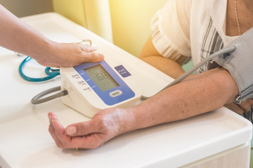 Nurse and elderly patient checking up blood pressure using upper arm blood pressure measuring monitor medical equipment in clinic examination room