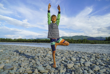 Young boy doing tree pose yoga on the shore of the beautiful mountain river.