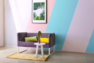 Framed picture of tropical leaves above couch in living room
