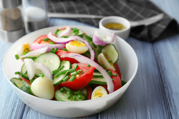 Healthy salad with cucumbers and eggs in bowl on table