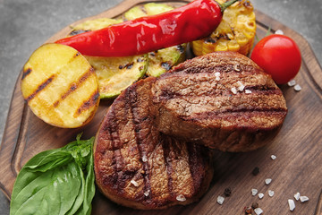 Wall Mural - Composition with tasty grilled steaks on table, closeup