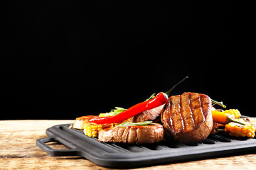 Wall Mural - Composition with tasty grilled steaks and vegetables on table