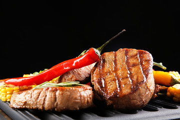 Composition with tasty grilled steaks and vegetables on table
