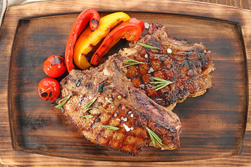 Wall Mural - Tasty grilled steaks with vegetables on wooden board