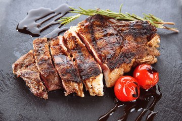 Tasty grilled steak with rosemary on slate plate