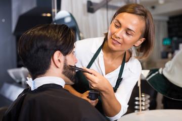 woman hairdresser shaving man's beard in barbershop